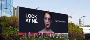 Bruised woman on billboard heals as passersby look at her