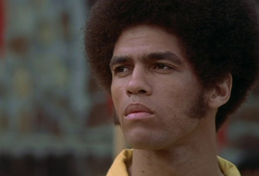Sporting a distinctive Afro hairstyle and sideburns, Jim Kelly made an ...